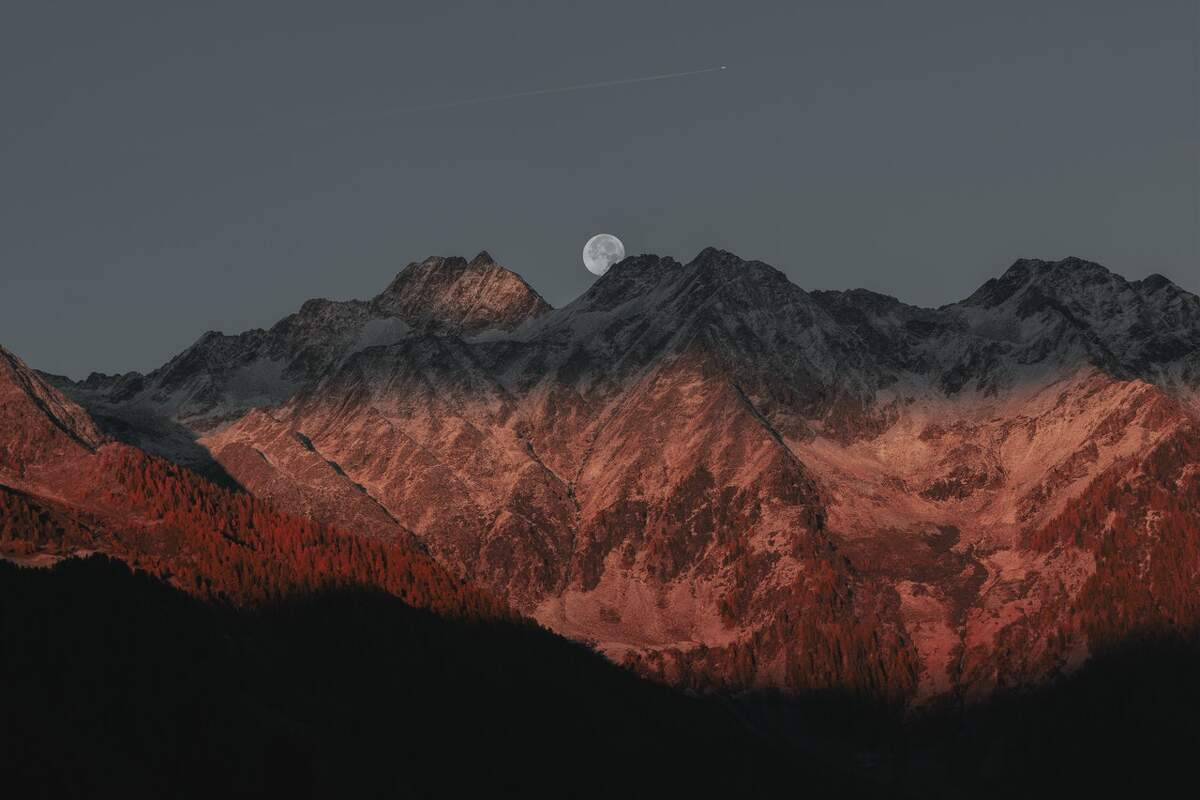 A full moon with some mountains on the front
