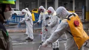 Agentes medioambientales fumigan una calle durante la crisis del coronavirus