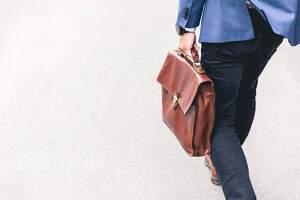 Hombre de negocios caminando con un maletín de piel en la mano