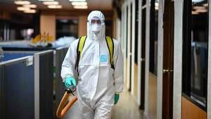 Sanitario desinfectando una sala durante la crisis del coronavirus