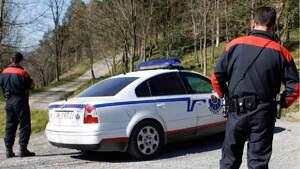 Dos agentes de la Ertzaintza junto a un coche patrulla