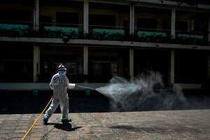 Un trabajador desinfectando una escuela de San Juan tras nuevos casos de coronavirus en Filipinas