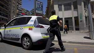Agente de la Policía Local junto al vehículo