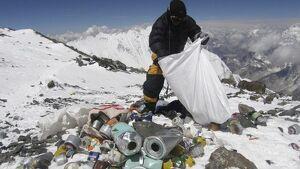 Un alpinista recoge basura en el camino a la cima del Everest