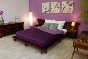 Lit aux draps violets dans une chambre violette peu éclairée
