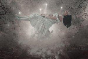 Femme en état d'hypnose dans un paysage de nuages et d'arbres