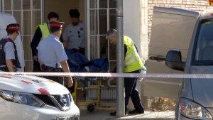 Els serveis funeraris traient el cos sense vida de la víctima mortal del crim d'Alfarràs del pis