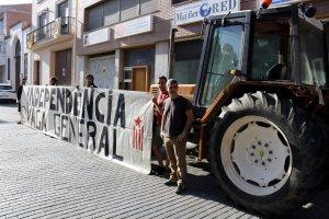 Diversos membres de l'Assemblea Pagesa al costat d'un tractor aparcat al carrer del col·legi electoral per l'1-O de les Borges Blanques