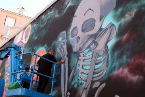 L'artista lleidatà Rulo López pintant el seu mural a la paret del costat de l'Ajuntament de Torrefarrera