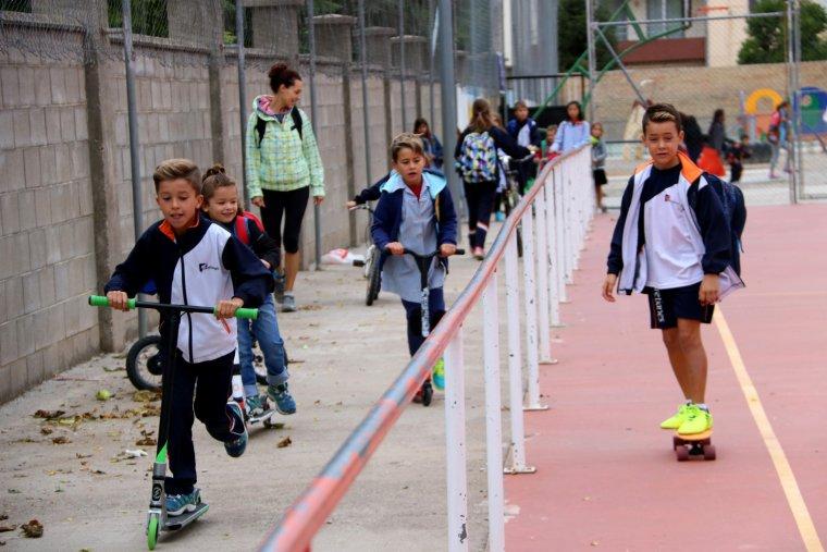 Un grup de nens i nenes arribant a l'escola amb bicicleta i patinet