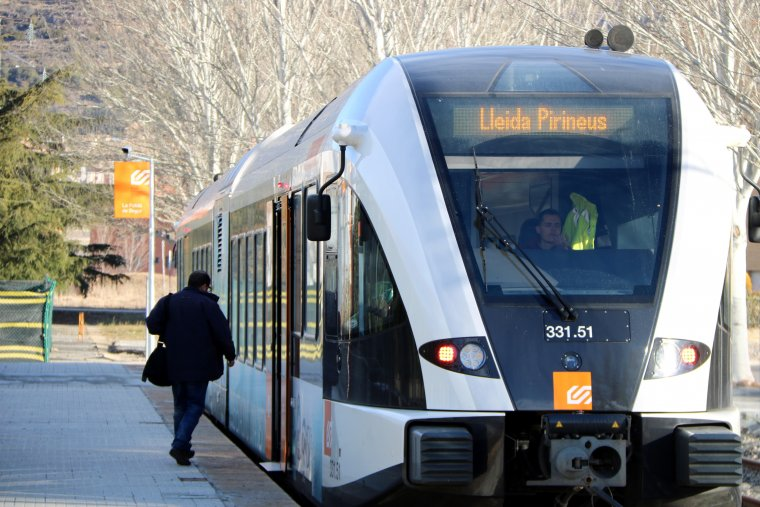 Un usuari pujant al tren a l'estació de la Pobla de Segur