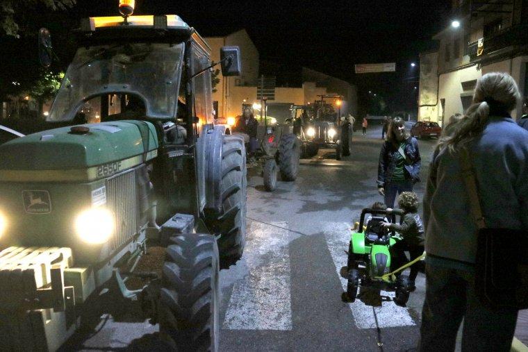 Diverses persones i tractors per Barbens en direcció a l'Ajuntament.