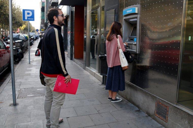 Dues persones retirant o esperant-se per treure diners en un caixer automàtic, seguint la convocatòria feta des de Crida per la Democràcia