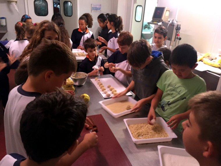 Imatge d'uns nens fent un taller de panellets amb codony