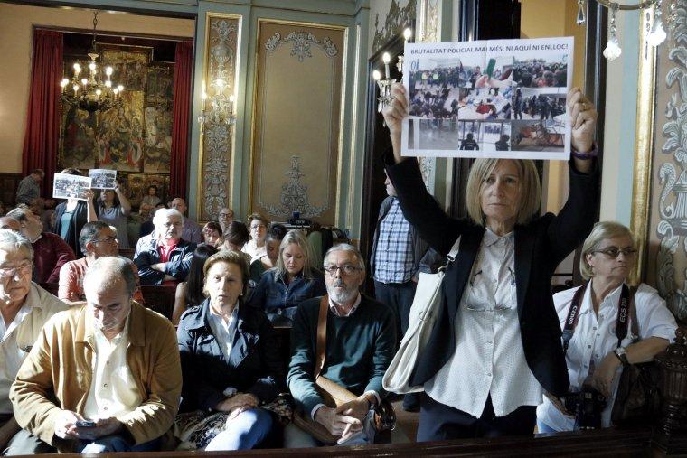Una dona mostra al Ple de l'Ajuntament de Lleida un cartell amb fotografies de les càrregues policials de l'1-O i el text 'Brutalitat policial mai més. Ni aquí ni enlloc'
