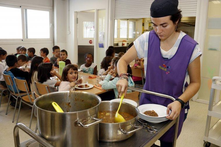 Una monitora servint menjar al plat al menjador escolar de l'Escola Maria Mercè Marçal de Tàrrega
