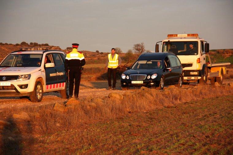 El cotxe de la funerària i una grua per remolcar la moto de la víctima arribant al lloc on un home n'ha matat un altre d'un tret en una zona rural de Santa Maria de Montmagastrell