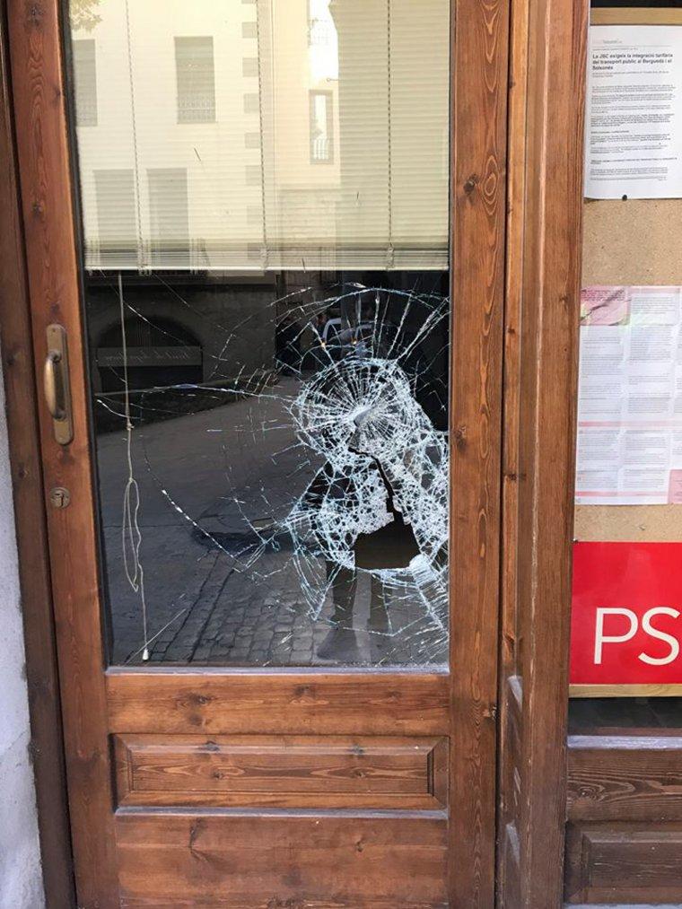 La porta de vidre del local del PSC de Solsona trencada per l'impacte d'una pedra