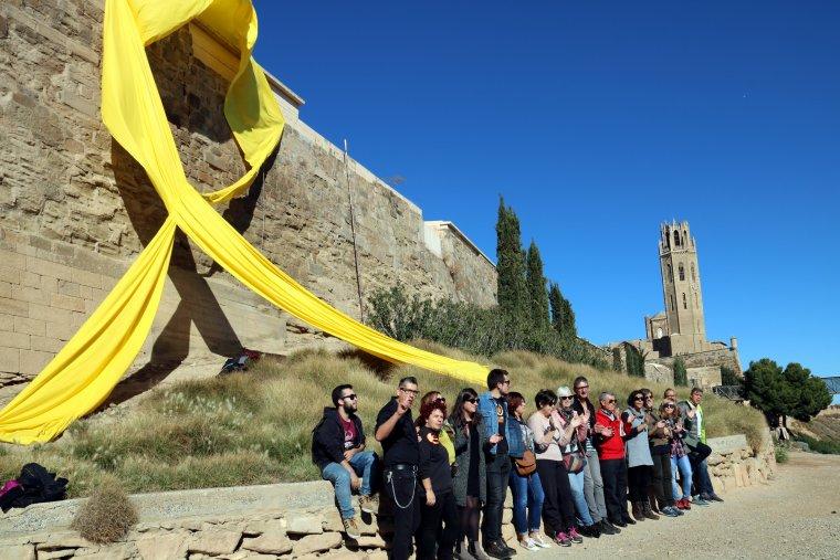 Un llaç groc gegant penjat al Baluard de la Llengua de Serp de la Seu Vella, amb la torre al fons, i membres del CDR Noguerola-Diputació de Lleida