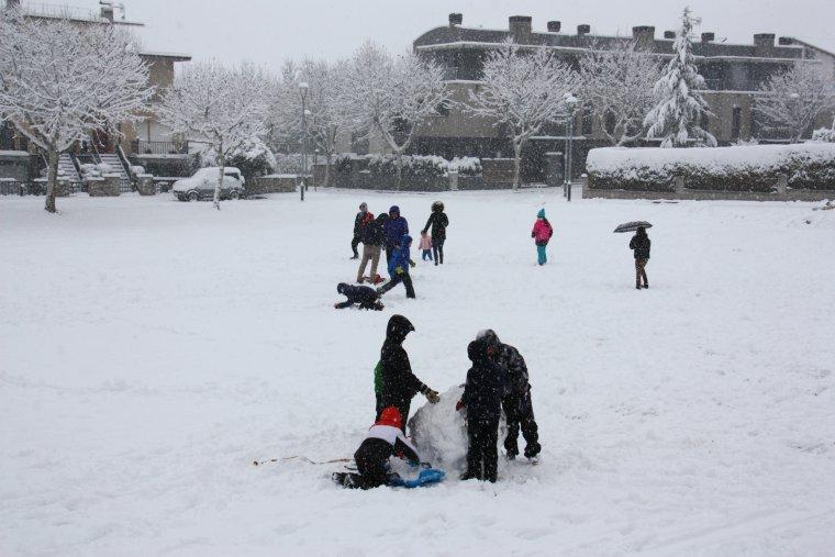 Diversos nens i nenes fent ninots de neu i jugant en un parc d'Oliana