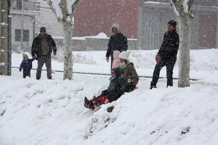 Dos nens a punt de tirar-se en trineu en un parc d'Oliana, el 28 de febrer de 2018