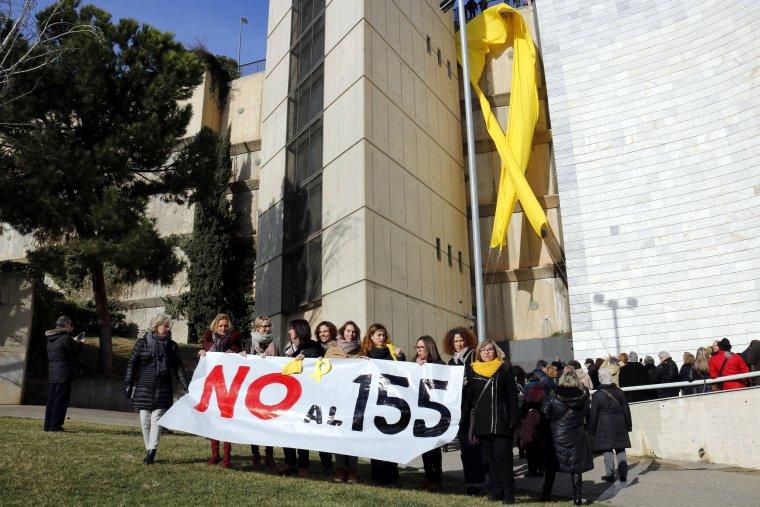 El llaç groc gegant penjant al costat dels jutjats de Lleida amb diverses persones concentrades i una pancarta contra el 155