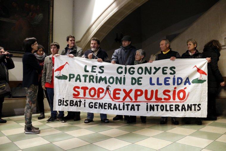 Membres d'Ipcena dins del Bisbat de Lleida amb un cartell que denuncia la retirada de nius de cigonya dels contraforts de la Catedral Nova