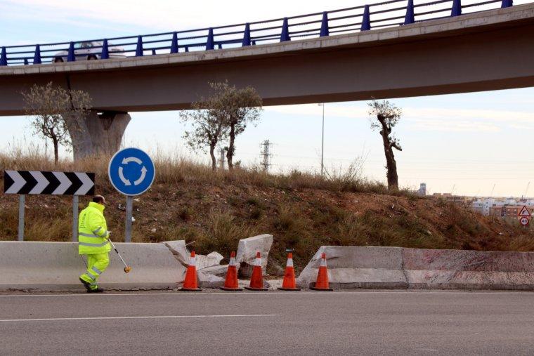 Pla obert d'un operari de carreteres prenent mesures a la rotonda de la T-11, a Tarragona, on s'ha produït l'accident, amb la tanca destrossada al seu costat