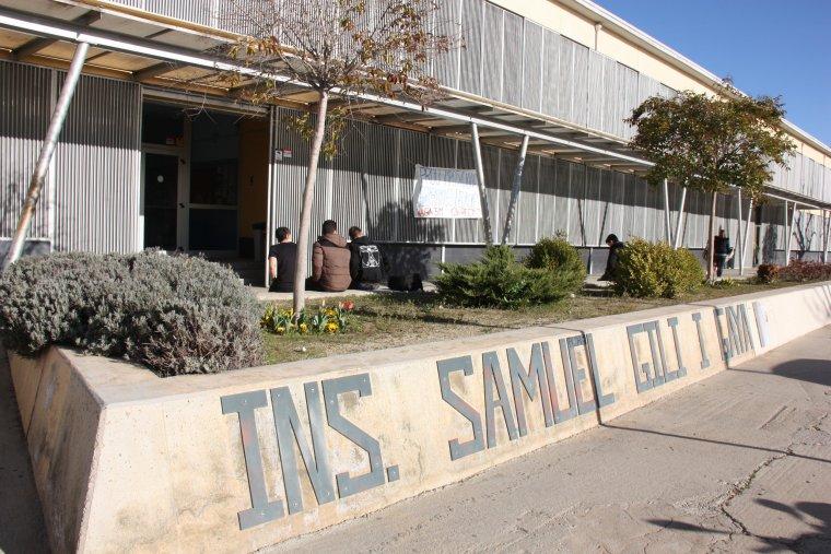 Tres alumnes asseguts d'esquena davant l'entrada de l'Institut Samuel Gili Gaya de Lleida