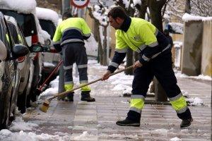 Pla mig on es poden veure dos operaris retirant neu amb escombres d'una vorera de Cervera
