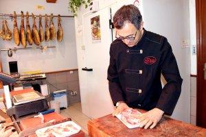 Un carnisser preparant una safata de carn de corder