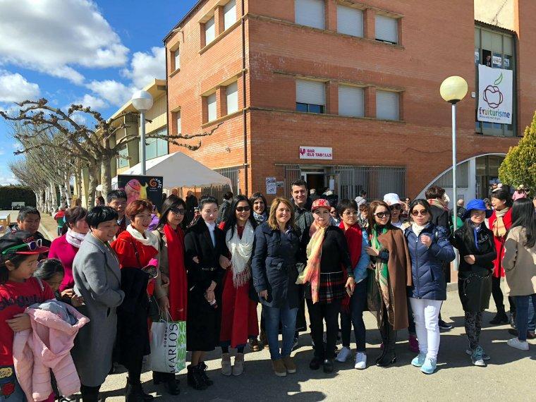 L'alcaldessa d'Aitona, Rosa Pujol (al centre) amb un grup de japonesos que han visitat els camps de fruiters florits