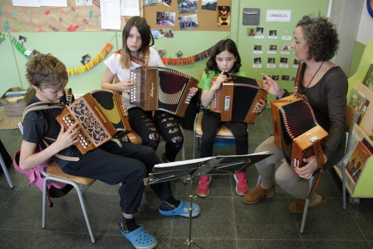 Pla general de tres alumnes d'acordió diatònic amb la seva mestra, fent l'activitat extraescolar que organitza l'Escola Folk del Pirineu