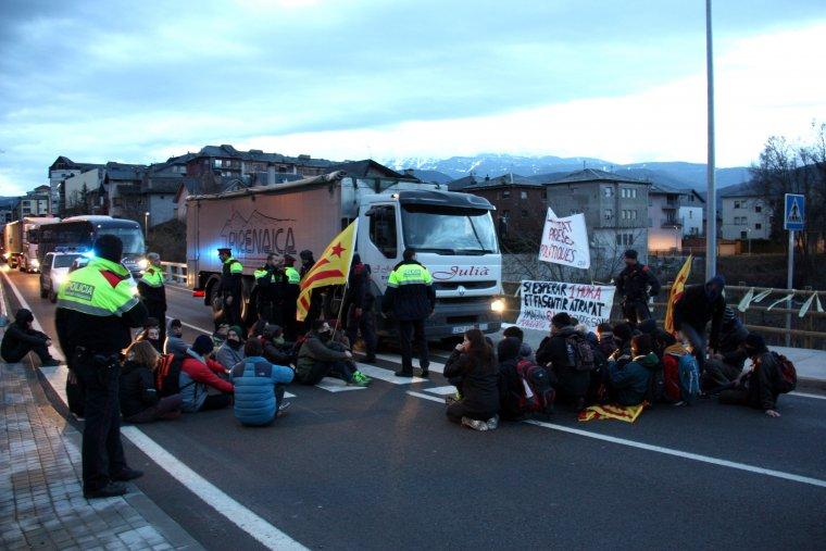 Pla general dels manifestants que han tallat l'N-260 a la Seu d'Urgell asseguts a la calçada, en un pas de vianants del costat del pont del riu Valira