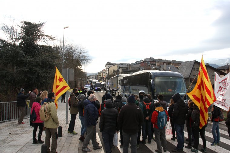 Pla general dels manifestants que tallen l'N-260 a la Seu d'Urgell amb agents antiavalots dels Mossos d'Esquadra arribant per parlar amb ells