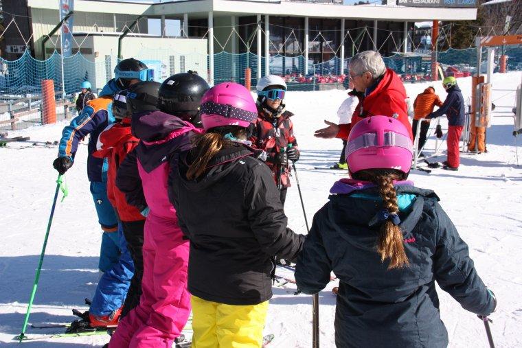 Pla general d'un grup d'esquiadors debutants parlant amb el director de l'escola d'esquí de la Molina, Hans Breitfuss, a peu de pistes