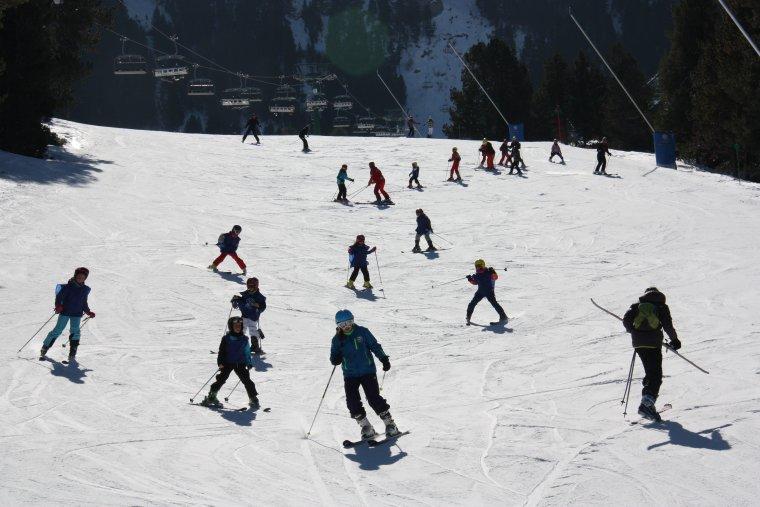 Pla general on es veuen diversos esquiadors baixant per una de les pistes d'esquí de la Molina