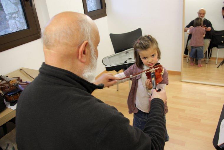 Pla mig d'un mestre de violí de l'Escola Folk del Pirineu fent classe a una nena petita a les instal·lacions d'Arsèguel