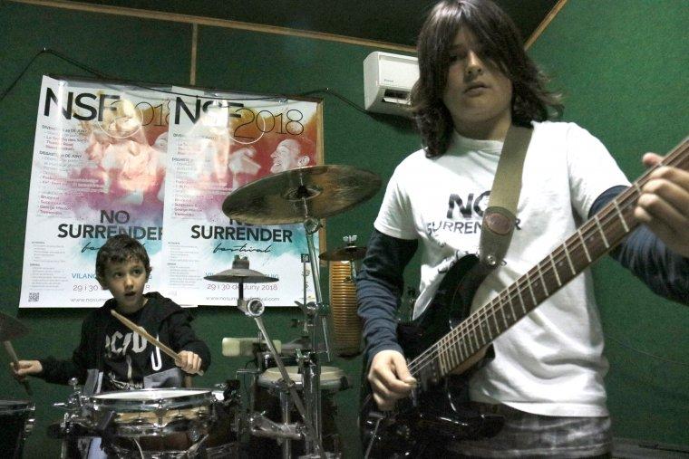 Pla mig on es pot veure dos alumnes de l'escola de música de Castellserà tocant la guitarra i la bateria assajant la cançó 'Badlands' per al No Surrender Festival