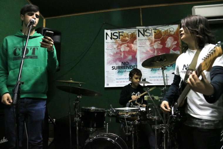 Pla mig on es pot veure tres alumnes de l'escola de música de Castellserà cantant, tocant la guitarra i la bateria assajant la cançó 'Badlands' per al No Surrender Festival