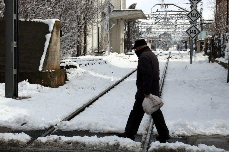 Pla mig on es pot veure una persona creuant la via del tren a Cervera en un entorn completament nevat