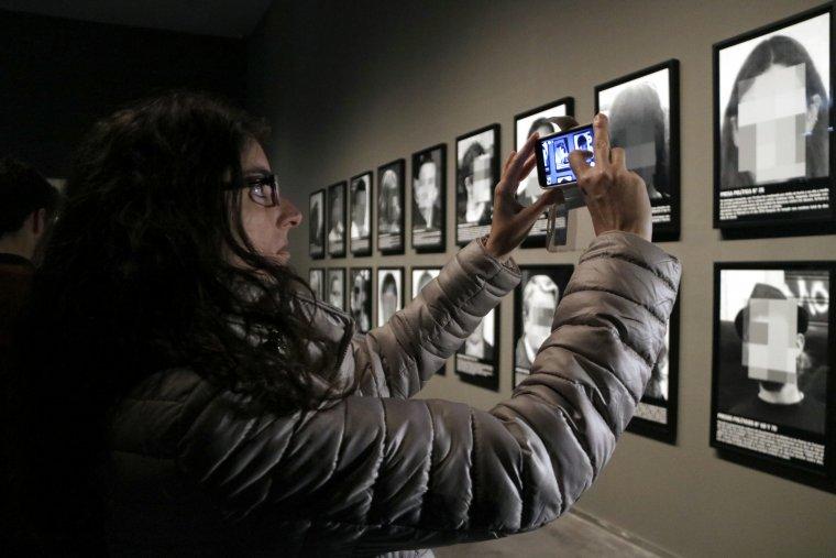 Pla tancat d'una noia que fa una foto a l'obra de Santiago Sierra sobre presos polítics al Museu de Lleida