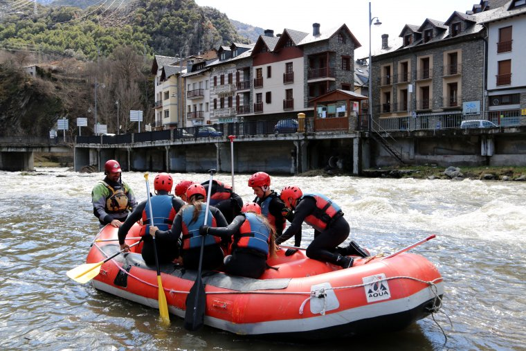 Primer pla d'una barca de ràfting amb el poble de Llavorsí, al Pallars Sobirà