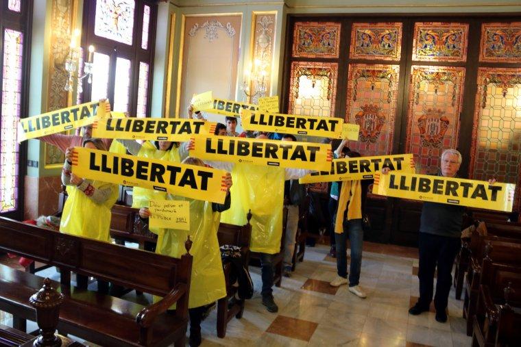 Un grup de persones vestides de color groc mostrant cartells amb el lema «llibertat» durant el Ple de la Paeria