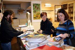 Imatge de dues dones que miren llibres al local de Cal Guitarreta