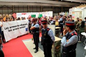 Una vintena de persones de la plataforma Desmilitaritzem l'Educació protestant davant de l'estand de l'Exèrcit
