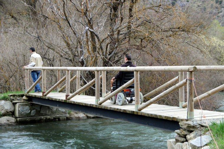 Dos homes passant per un pont sobre el riu Noguera Pallaresa, en un itinerari adaptat per persones amb cadires de rodes