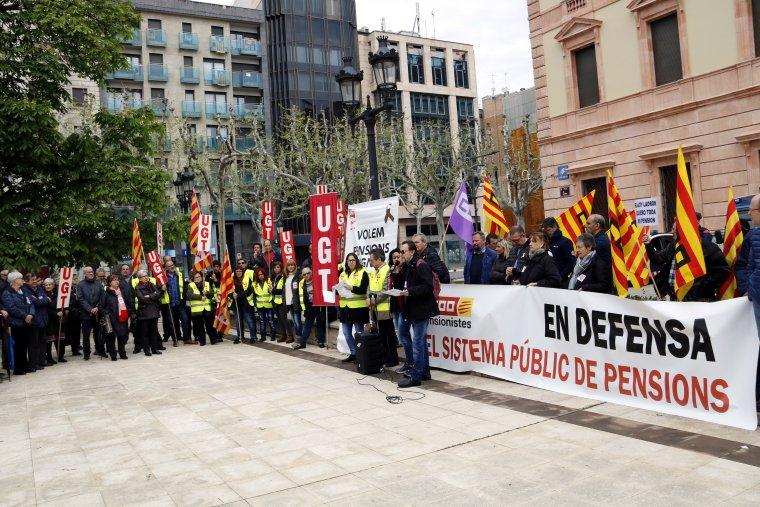 Imatge general de les principals pancartes i de part dels concentrats per reclamar unes pensions dignes a la protesta convocada per UGT i CCOO