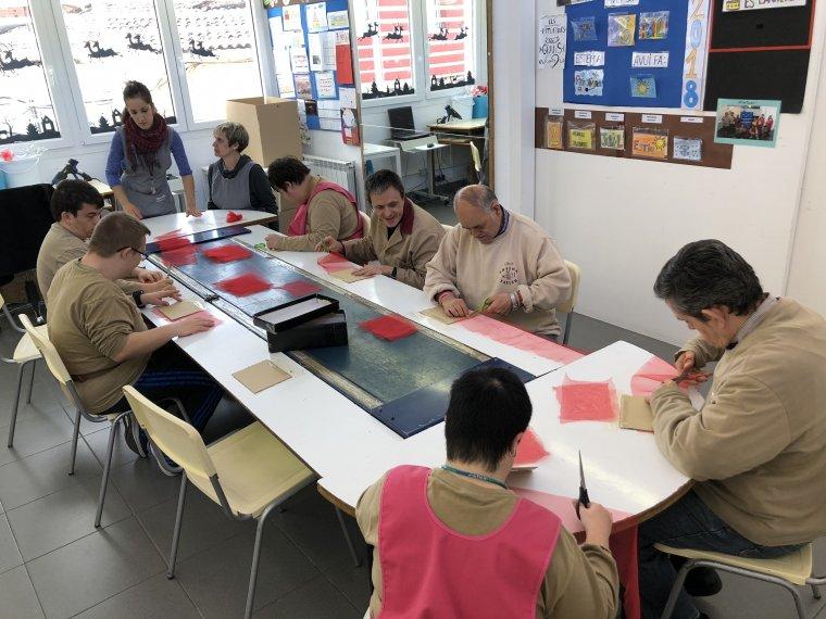 Persones del Centre Ocupacional d'ILERSIS Fundació preparant les roses de Sant Jordi.