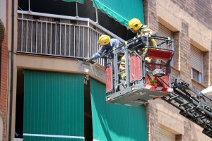 Efectius dels Bombers de la Generalitat inspeccionant el tros de cornisa